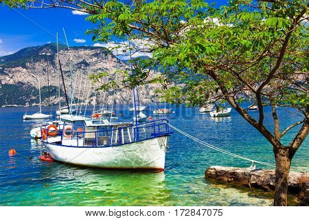 Pictorial scenery with boats in beautiful lake Lago di Garda. Italy