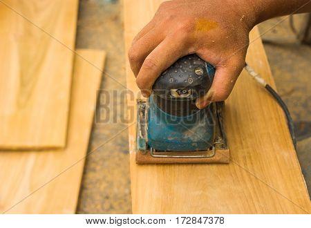 Carpenter's hands using sander on wooden  in workshop,Electrical sander tool,power sander,Man Working with an Electric Sander