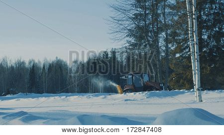 Tractor removing snow from the winter road in the forest.