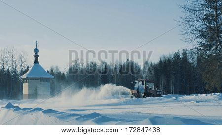 Tractor driving backwards and removing snow from the winter road.