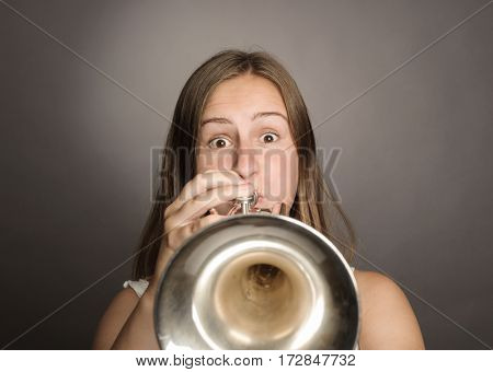 woman playing trumpet on a gray background