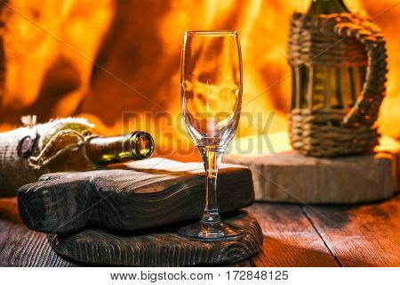 Empty glass for sparkling wine and open bottles. Fire in fireplace on the background