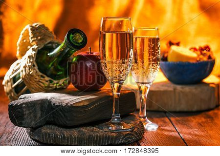 Sparkling wine and various fruit. Fireplace lighting on the background