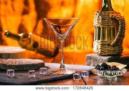 Cocktail in martini glass. Olives and lemon for serving on bar counter. Fireplace background
