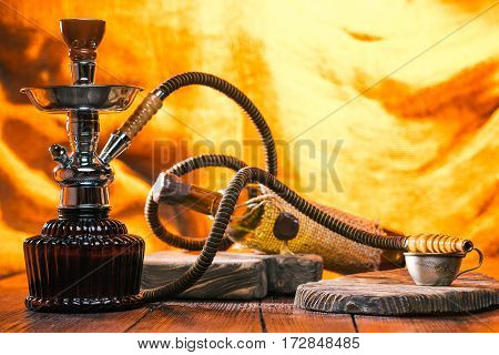 Hookah, coffee cup and wine over fire light background