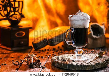 Glass of irish coffee cocktail, coffee mill, beans and cinnamon sticks on rustic wooden boards. . Fire light in fireplace on the background