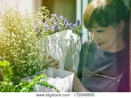Young florist woman decorating flower bouquet