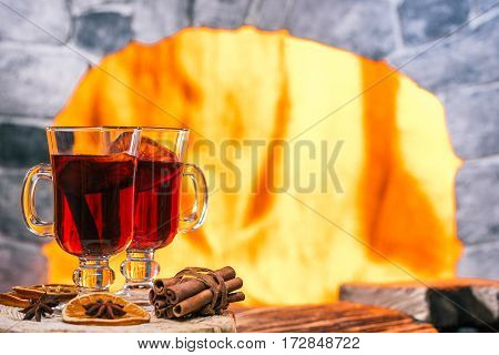 Spiced mulled wine in two glasses on the wooden serving board. Hearth on the background