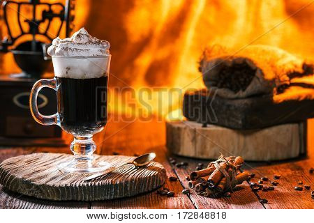 Glass of irish coffee cocktail. Cinnamon sticks, coffe beans and mill. Fire light in fireplace on the background