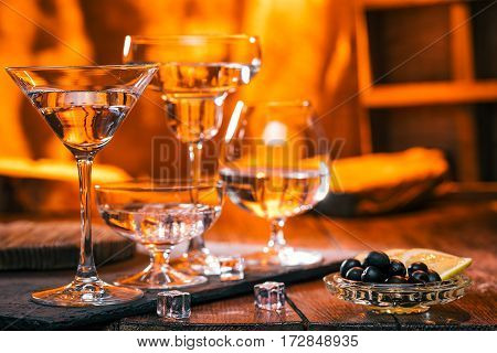 Various glasses on bar counter. Fire light on the background