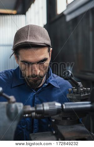 Close-up of bearded constructor looking attentively at working machine