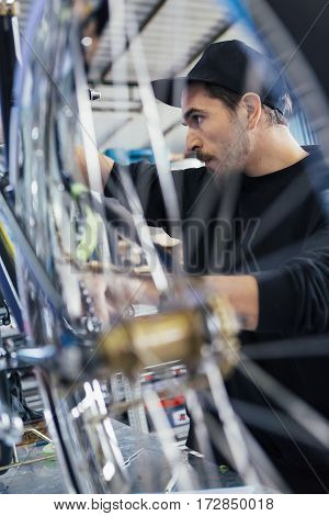 Close-up of craftsman looking at bicycle. Wheel on foreground