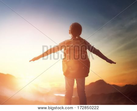 Little child is looking at sunset. Young traveller with backpack.