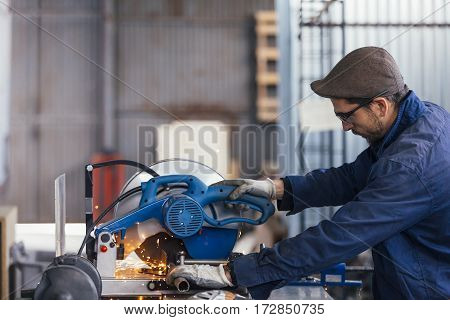 Bearded man in glasses working with metal bars on saw machine