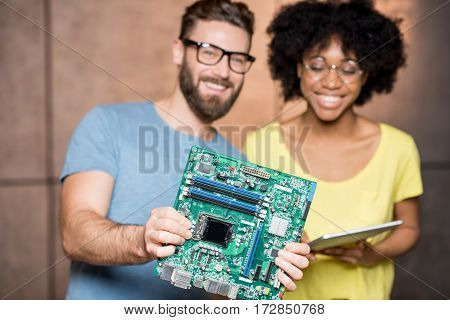 Multi ethnic programmers dressed casually showing computer motherboard standing on the wall background indoors