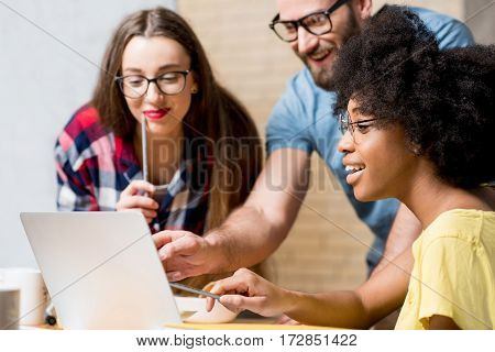 Multi ethnic coworkers dressed casually in colorful clothes working during the meeting at the office with laptop and documents