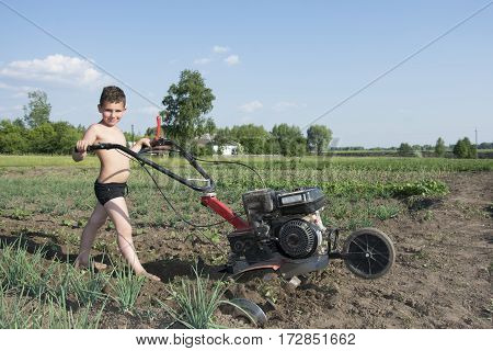 Spring bright sunny day in the garden a little boy plowing the ground the motor-block.