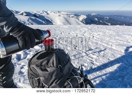 Pouring tea from a thermos into a cup in the winter at the top of the mountains.
