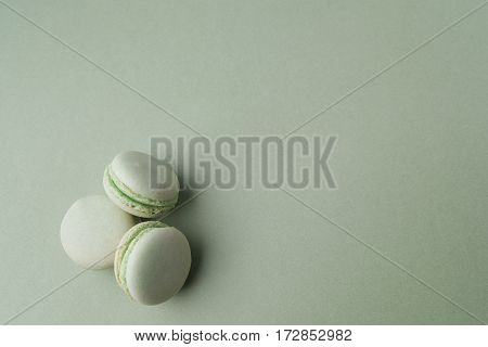 Green macarons on green background. Top view