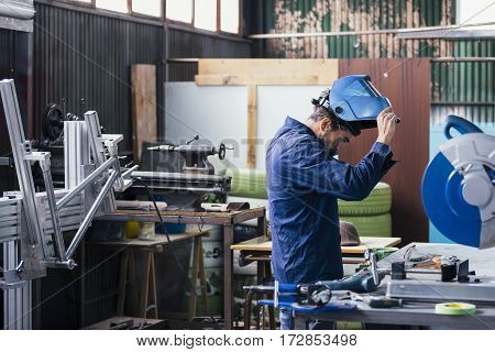 Professional craftsman putting on mask for welding metal