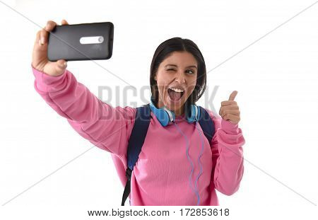 young attractive and happy woman or student girl with backpack and headphones taking selfie photo with mobile phone smiling ecstatic having fun isolated on white background