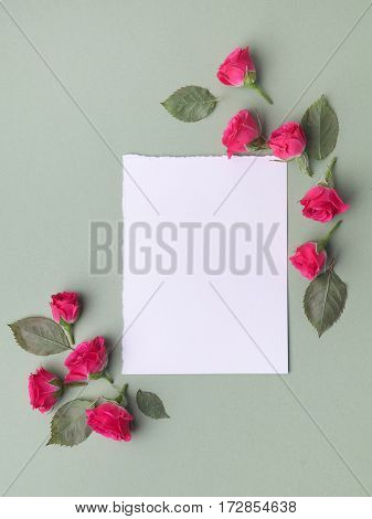 Framework from roses on green background. Flat lay. Top view