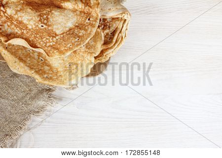 flat layout of a pile of pancakes on a light wooden table top view / lush appetizing breakfast