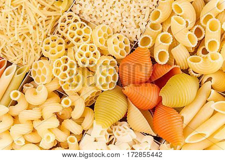 Pasta background assortment of different kinds italian macaroni in chess cells top view. Healthy traditional food backdrop.