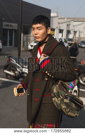 MILAN ITALY - FEBRUARY 22: Fashionable man poses outside Gucci fashion show building during Milan Women's Fashion Week on FEBRUARY 22 2017 in Milan.