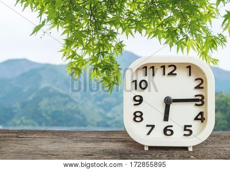 Closeup white clock for decorate show a quarter past six or 6:15 a.m. on blurred mountain view background