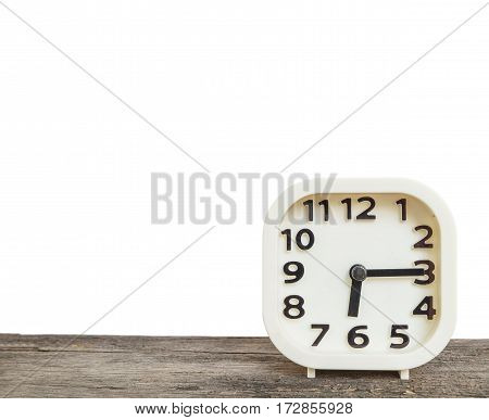 Closeup white clock for decorate show a quarter past six or 6:15 a.m. on old brown wood desk isolated on white background with copy space