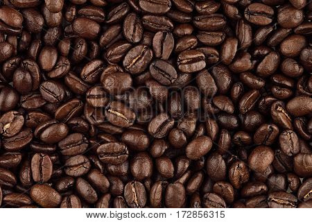 Roasted coffee beans closeup top view as background.