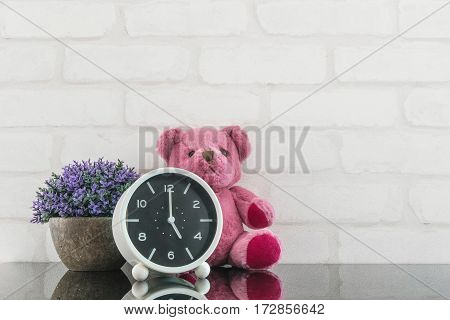 Closeup black and white alarm clock for decorate in 5 o'clock with bear doll and plant on black glass table and white brick wall textured background with copy space