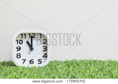 Closeup white clock for decorate in 11 o'clock on green artificial grass floor and cream wallpaper textured background with copy space