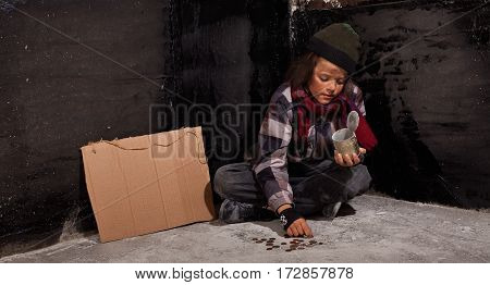 Young and dirty beggar boy counting coins - sitting on the ground by a blank cardboard sign with copy space