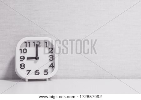 Closeup white clock for decorate in 9 o'clock on white wood desk and cream wallpaper textured background in black and white tone with copy space