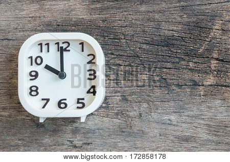 Closeup white clock for decorate in 10 o'clock on old wood floor textured background with copy space