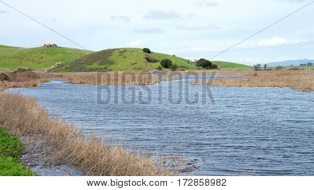 Recent rains relieve Drought conditions in California by flooding marsh land. Previously dried up lake bed with pier under water in Coyote Hills Northern California