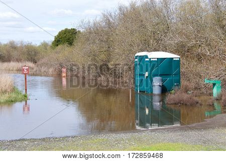 Portable bathroom and drinking fountain at start of pedestrian trail flooded with flood water higher on the trail submerging warning signs for hikers. No feeding wildlife. no horses on trail.