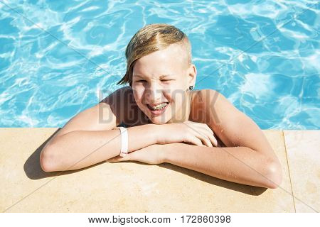 Teenager with brackets on teeth and piercing relaxes in the pool