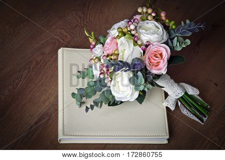 bouquet of artificial roses berries ranunkulyus; buttercup sprigs of eucalyptus lies on the wedding photo book on the wooden floor
