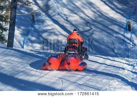 Red big banana catamaran boat for tubing dragging by snowmobile in winter