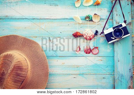 Summer background - The concept of leisure travel in the summer on a tropical beach seaside. retro camera with straw hat hanging on wood wall background. vintage color tone styles.