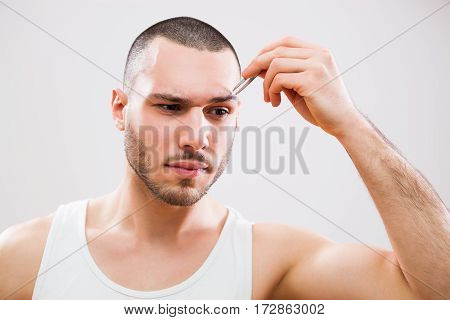 Young man is plucking eyebrows with tweezers. poster