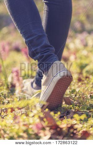 Girl walking in the flowery meadow outdoors.