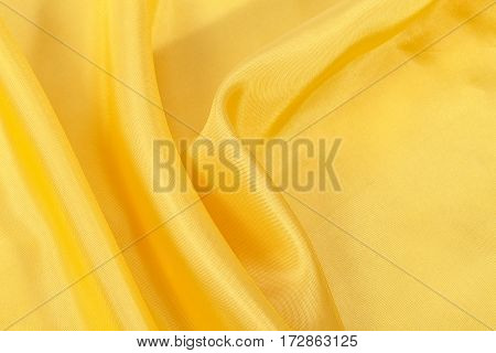 Silk background texture of yellow shiny fabric close up