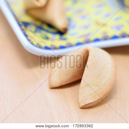 One whole fortune cookie is laying on the table