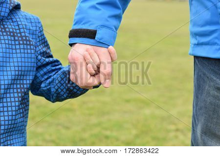 Father and son are holding the hands