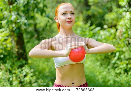 Young red female fitness instructor exercising with small ball in green park