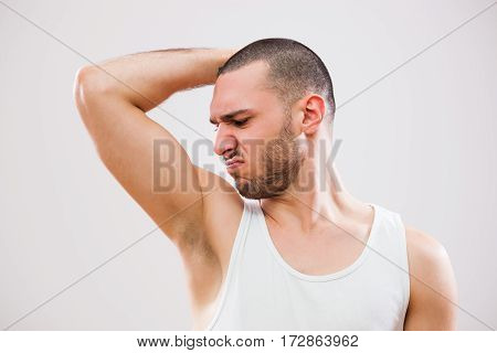 Young man is smelling his armpit before shower.